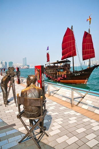 China, Hong Kong, Tsim Sha Tsui, Tsim Sha Tsui East Promenade, a sightseeing junk passes the Avenue of the Stars with sculptures paying homage to the Hong Kong film industry : Stock Photo
