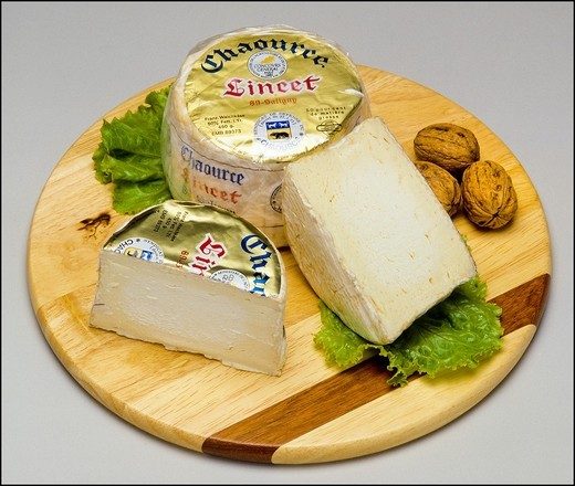 Whole Chaource French cheese and wedge with nuts on wooden board : Stock Photo