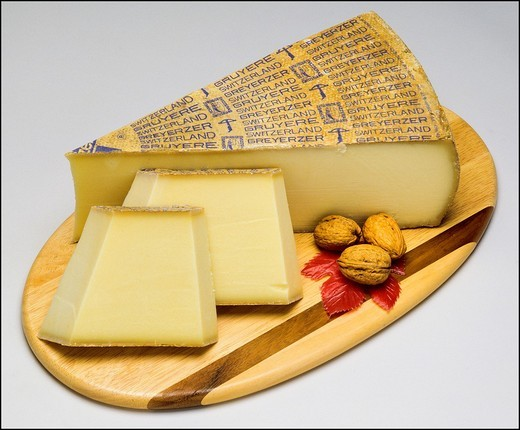 Stock Photo: 1566-702071 Gruyère Swiss cheese and wedges with nuts on wooden board