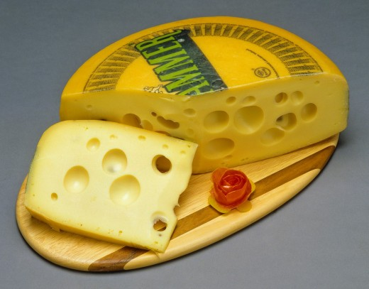 Leerdammer Dutch cheese and slice on wooden board : Stock Photo