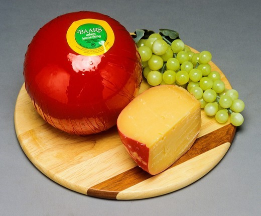 Whole Edam Dutch cheese and wedge with white grape on wooden board : Stock Photo
