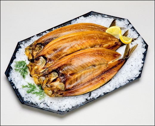 Kipper smoked Herring fishes on platter with ice : Stock Photo