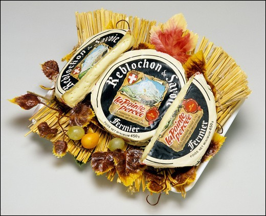 Stock Photo: 1566-702541 Whole Reblochon de Savoie French cheese and wedges on straw mat