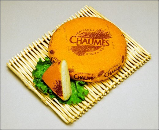 Stock Photo: 1566-702542 Chaumes French cheese and wedge on wooden mat