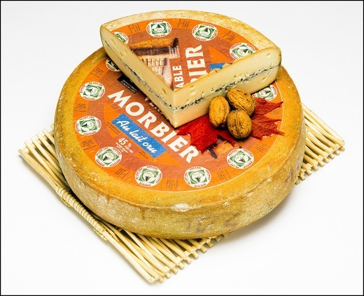 Stock Photo: 1566-702544 Whole Morbier French cheese and wedge on wooden mat