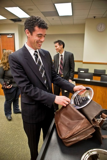 Stock Photo: 1566-702673 A proud student looks at his prize from the moot court of the law school of the University of California -- a prestigious extracurricular activity in which participants take part in simulated court proceedings, usually in an appellate court or arbitral ca. A proud student looks at his prize from the moot court of the law school of the University of California -- a prestigious extracurricular activity in which participants take part in simulated court proceedings, usually in an appellate court or