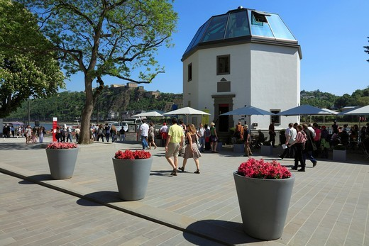 Germany. Koblenz. Germany. Koblenz, Rhine, Moselle, Maifeld, Eifel, Hunsrueck, Westerwald, Rhineland-Palatinate, tourists on the Rhine promenade, Rhine bank, Pegelhaus, water gauge house, flower buckets, in the background the Ehrenbreitstein Fortress, UNESCO World Heritage Site Oberes Mittelrheintal, Upper Middle Rhine : Stock Photo