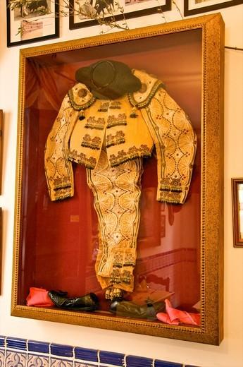 indoor decoration of restaurant La Cueva dedicated to bull fighting art a matador costume hat and shoes Sevilla Andalucia Spain : Stock Photo
