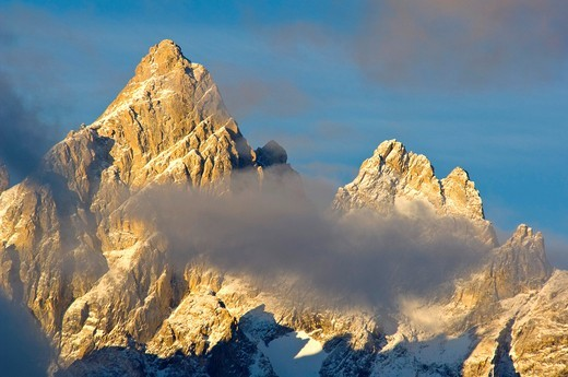 Stock Photo: 1566-712384 Sunrise light and clouds on the summit peak of the Grand Teton mountain, Grand Teton National Park, Wyoming
