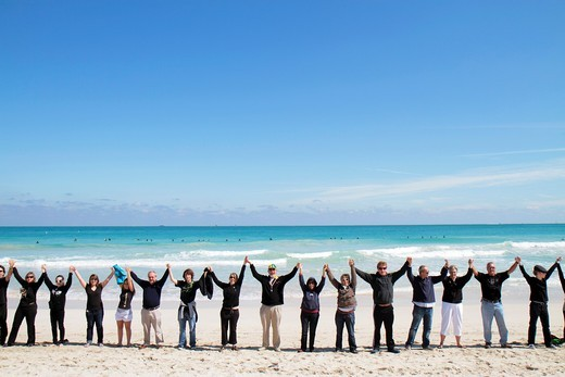 Florida, Miami Beach, Surfrider Foundation, No Offshore Florida Oil Drilling Protest, black clothing represents oil, hold hands, unity, Atlantic Ocean, surf, : Stock Photo