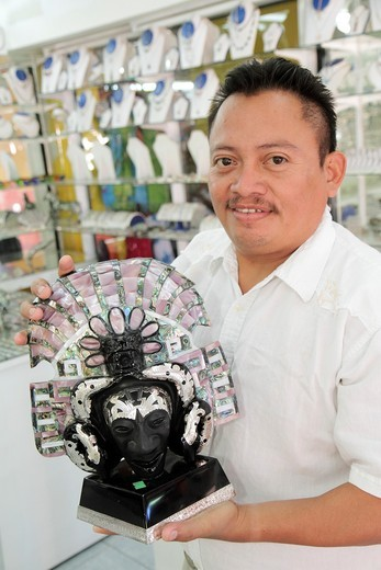 Stock Photo: 1566-714621 Mexico, Yucatán Peninsula, Quintana Roo, Cancun, Mercado 28, market, shopping, store, souvenir, Mayan inspired mask, stone carving, silver, mother of pearl inlay, local handicraft, jewelry, Hispanic, man, salesman, merchandise,