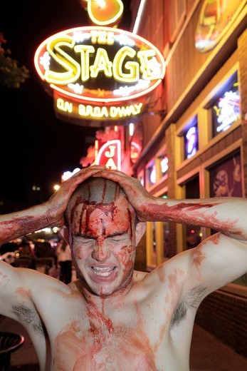 Tennessee, Nashville, ´Music City USA´, downtown, Lower Broadway, business strip, neon light, sign, honky tonk, ´The Stage´, man, young adult, Zombie Walk, smeared blood, night, nightlife, : Stock Photo