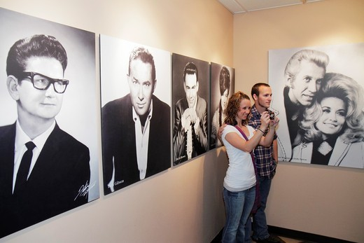 Stock Photo: 1566-715275 Tennessee, Nashville, Country Music Hall of Fame and & Museum, Historic RCA Studio B tour, music industry, recording, preservation, exhibition, historic photographs, Roy Orbison, Dolly, Don Gibson, Porter Wagoner, man, woman, couple, taking picture,