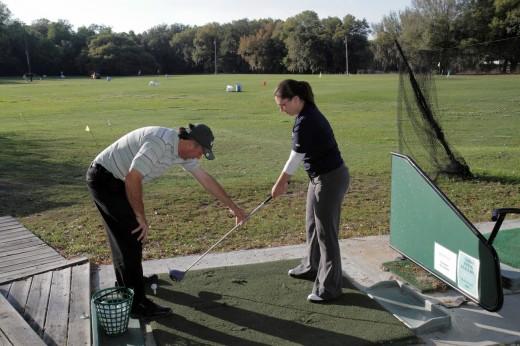 Florida, Lakeland, golf driving range, practice, sports, swing, swinging, hitting, balls, lesson, teacher, student, man, woman, coaching, : Stock Photo