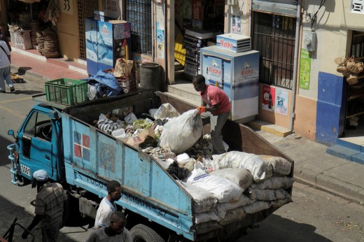 Dominican Republic, Santo Domingo, Ciudad Colonial, Mercado Modela, market, street scene, trash, waste management, collection, disposal, garbage truck, Black, man, worker, dirty job, sack, : Stock Photo