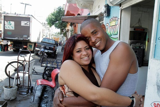 Dominican Republic, Santo Domingo, Ciudad Colonial, Mercado Modela, Hispanic, Black, sidewalk, man, woman, couple, relationship, young adult, embrace, romance, darker skin, lighter skin, smile, : Stock Photo