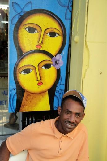 Dominican Republic, Santo Domingo, Ciudad Colonial, Calle Isabel La Catolica, Black, souvenir vendor, Black, man, sitting, painting, female, big eyes, : Stock Photo