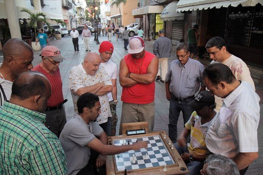 Dominican Republic, Santo Domingo, Ciudad Colonial, Calle el Conde Peatonal, pedestrian mall, Hispanic, Black, man, men, leisure, loitering, chess, board game, strategy, tactic, observe, younger, older, street scene, : Stock Photo