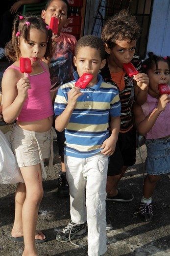 Stock Photo: 1566-715557 Dominican Republic, Santo Domingo, Ciudad Colonial, Calle Padre Billini, urban residential street, neighborhood, eating ice cream, popsicle, Hispanic, boy, girl, child, group, frozen treat, popsicle,