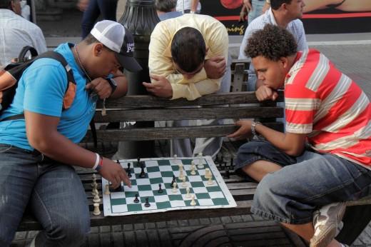 Dominican Republic, Santo Domingo, Ciudad Colonial, Calle el Conde Peatonal, pedestrian mall, bench, Hispanic, mestizo, man, boy, teen, chess, board game, leisure, pastime, tactic, thinking, observe, : Stock Photo
