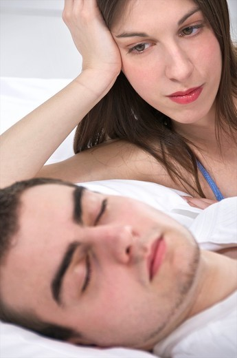 Young couple in bed, she is wide awake while he is asleep and snoring : Stock Photo