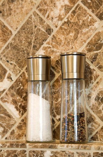 Stock Photo: 1566-727424 Close-up of Salt and Peppercorn Shakers against a Marble Wall background in a Luxurious Kitchen  This image is property released  PR0083