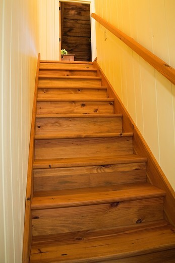 Pinewood stairs leading to the upstairs floor in an Old Canadiana 1722 cottage style fieldstone and wooden siding Residential Home, Quebec, Canada  This image is property released PR0133 but not available for billboard, outdoor advertising, product packag. Pinewood stairs leading to the upstairs floor in an Old Canadiana 1722 cottage style fieldstone and wooden siding Residential Home, Quebec, Canada  This image is property released PR0133 but not available for billboard, outdoor advertising, pr : Stock Photo