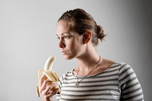 Young woman eating a banana : Stock Photo