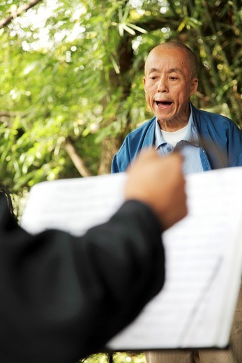 A man singing Peking Opera accompanied by Erhu a traditional two string musical instrument in Green Lake Park Cui Hu Park  Kunming  China : Stock Photo