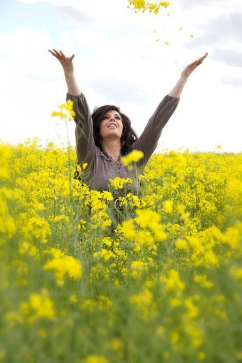 A happy young caucasian woman in a field of canola : Stock Photo