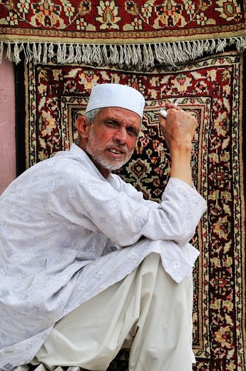 Muslim man selling traditional carpet by the road : Stock Photo