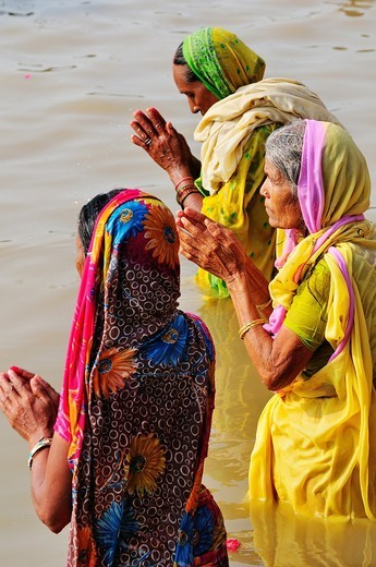 Pilgrims women bathing and praying at the ghat by the Ganges river : Stock Photo