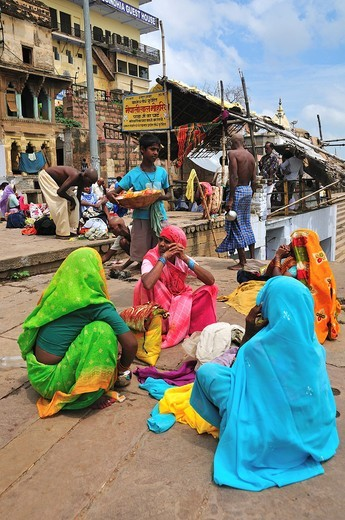 Pilgrims relaxing after bathing at the ghat by the Ganges river : Stock Photo