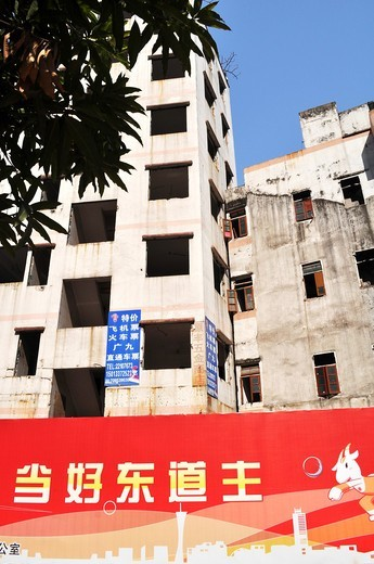 Guangzhou (China): old apartment buildings expropriated by the local authorities for property speculation, covered with outdoors depicting a 'modern city of the future', in Tianhe : Stock Photo