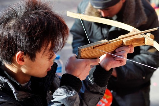 Beijing (China): a young man playing with a crossbow at the Dongyue Temple during the Spring Festival : Stock Photo