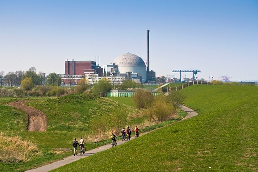 Stock Photo: 1566-744768 Cyclists pedaling towards the nuclear power plant of Stade, Lower Saxony, Germany, Europe
