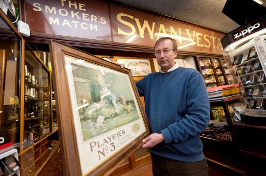 Peter Lloyd - the owner of A E Lloyd and Son Tobacconists, established 1890, Aberystwyth Wales UK, holding an old advert for Players No3 Cigarettes : Stock Photo