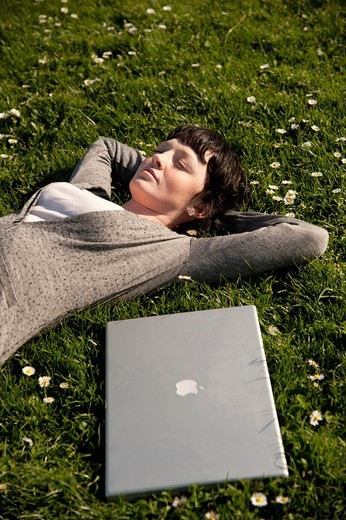 Stock Photo: 1566-748880 A young woman UK university student with her apple laptop computer outdoors on a sunny warm day