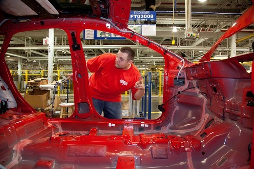 Stock Photo: 1566-752738 Wayne, Michigan - Workers assemble the 2012 Ford Focus at Ford Motor Co ´s Michigan Assembly Plant  The workers are members of the United Auto Workers  They wore red t-shirts in solidarity with public employees in Wisconsin and other states fighting again. Wayne, Michigan - Workers assemble the 2012 Ford Focus at Ford Motor Co ´s Michigan Assembly Plant  The workers are members of the United Auto Workers  They wore red t-shirts in solidarity with public employees in Wisconsin and other states fi