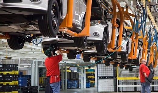 Wayne, Michigan - Workers assemble the 2012 Ford Focus at Ford Motor Co ´s Michigan Assembly Plant  The workers are members of the United Auto Workers  They wore red t-shirts in solidarity with public employees in Wisconsin and other states fighting again. Wayne, Michigan - Workers assemble the 2012 Ford Focus at Ford Motor Co ´s Michigan Assembly Plant  The workers are members of the United Auto Workers  They wore red t-shirts in solidarity with public employees in Wisconsin and other states fi : Stock Photo
