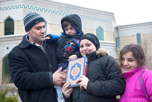 Dearborn, Michigan - Malak Bazzi, 10, stands with her family as she holds a copy of the Quran outside the Islamic Center of America  They were part of a crowd gathered in opposition to Rev  Terry Jones, the anti-Islamic Florida pastor who burned the Quran. Dearborn, Michigan - Malak Bazzi, 10, stands with her family as she holds a copy of the Quran outside the Islamic Center of America  They were part of a crowd gathered in opposition to Rev  Terry Jones, the anti-Islamic Florida pastor who burn : Stock Photo