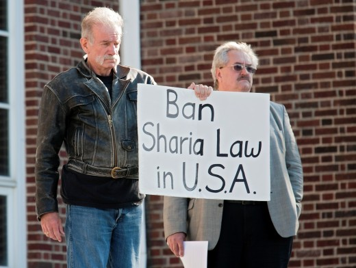 Dearborn, Michigan - Rev  Terry Jones left, the anti-Islamic Florida pastor who burned the Quran, held a demonstration ´against sharia and jihad´ at Dearborn City Hall  A large crowd of mostly Arab-Americans gathered across the street to oppose him : Stock Photo