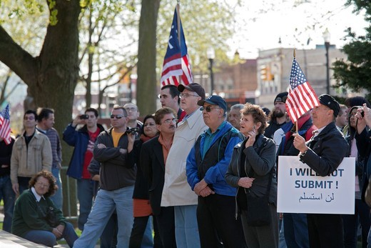Dearborn, Michigan - Supporters of Rev  Terry Jones, the anti-Islamic Florida pastor who burned the Quran, listen as Jones speaks at a rally ´against sharia and jihad´ at Dearborn City Hall  A large crowd of mostly Arab-Americans gathered across the stree. Dearborn, Michigan - Supporters of Rev  Terry Jones, the anti-Islamic Florida pastor who burned the Quran, listen as Jones speaks at a rally ´against sharia and jihad´ at Dearborn City Hall  A large crowd of mostly Arab-Americans gathered acro : Stock Photo