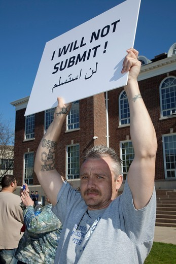 Dearborn, Michigan - A supporter of Rev  Terry Jones, the anti-Islamic Florida pastor who burned the Quran, at a demonstration Jones held ´against sharia and jihad´ at Dearborn City Hall  A large crowd of mostly Arab-Americans gathered across the street t. Dearborn, Michigan - A supporter of Rev  Terry Jones, the anti-Islamic Florida pastor who burned the Quran, at a demonstration Jones held ´against sharia and jihad´ at Dearborn City Hall  A large crowd of mostly Arab-Americans gathered across  : Stock Photo