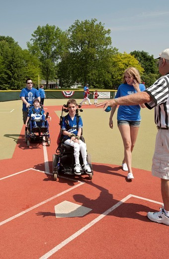 Southfield, Michigan - Children with disabilities play baseball in the Miracle League  Each child has a buddy who volunteers to help the child, as needed, hit, field, and round the bases : Stock Photo