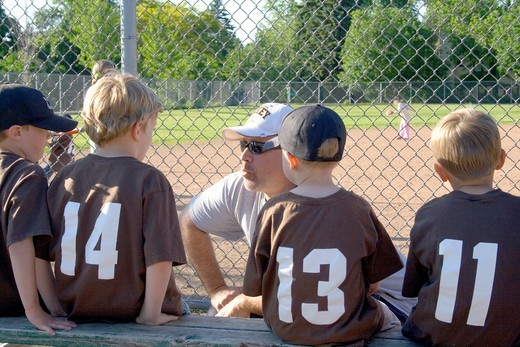 Coach speaking instructing young baseball players on the bench  St Paul Minnesota MN USA : Stock Photo