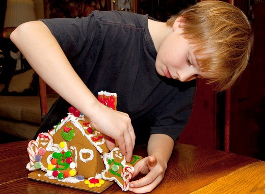 Stock Photo: 1566-754427 Boy age 10 concentrating on decorating Christmas gingerbread house  St Paul Minnesota USA