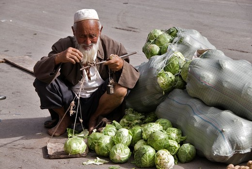 Old man weighing cauliflowers in a market  Kashgar, Xinjiang, China : Stock Photo
