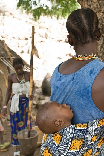 African bedik woman carrying a child while others pound peanuts for food, Iwol village, Bassari country, Senegal, Africa : Stock Photo