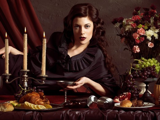 High fashion photo of a beautiful woman lying on a table with remains of a festive dinner : Stock Photo